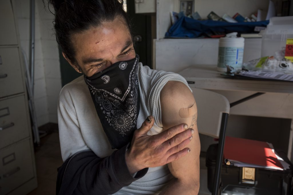 A white man with black hair and a black bandana wrapped around his face as a mask pats his arm. A bandaid can be seen where he just received his COVID vaccine.