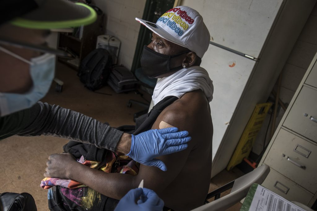 """A gloved doctor puts a bandaid on the arm of a Black man in a hat that reads """"good vibes"""" after administering his vaccine."""