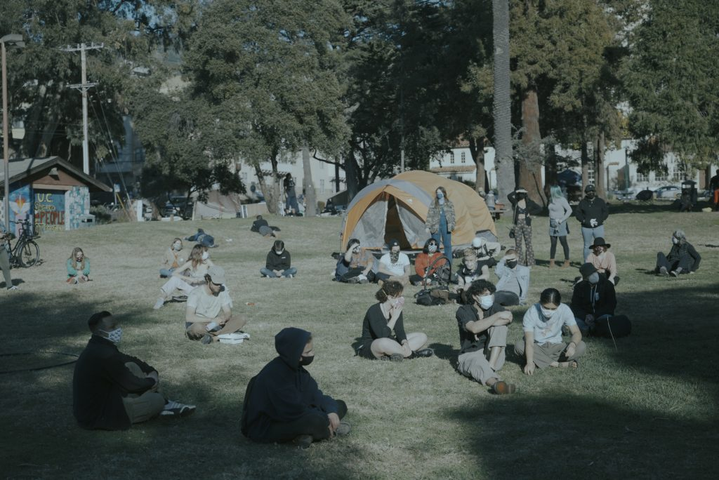 Students sit in the grass at the park, spaced apart wearing masks, in a meeting to discuss organizing strategies to prevent development at the park. Tents can be seen in the background.