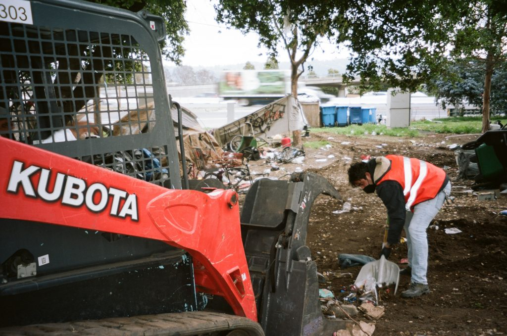 Cordova Morales shoves a pile of garbage into the front loader—an orange machine with sharp teeth at the front.