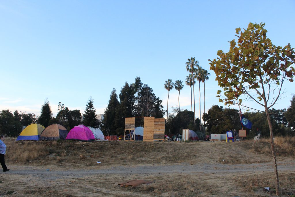 A homeless encampment with a colorful arrangement of tents and tall palm trees in the background.