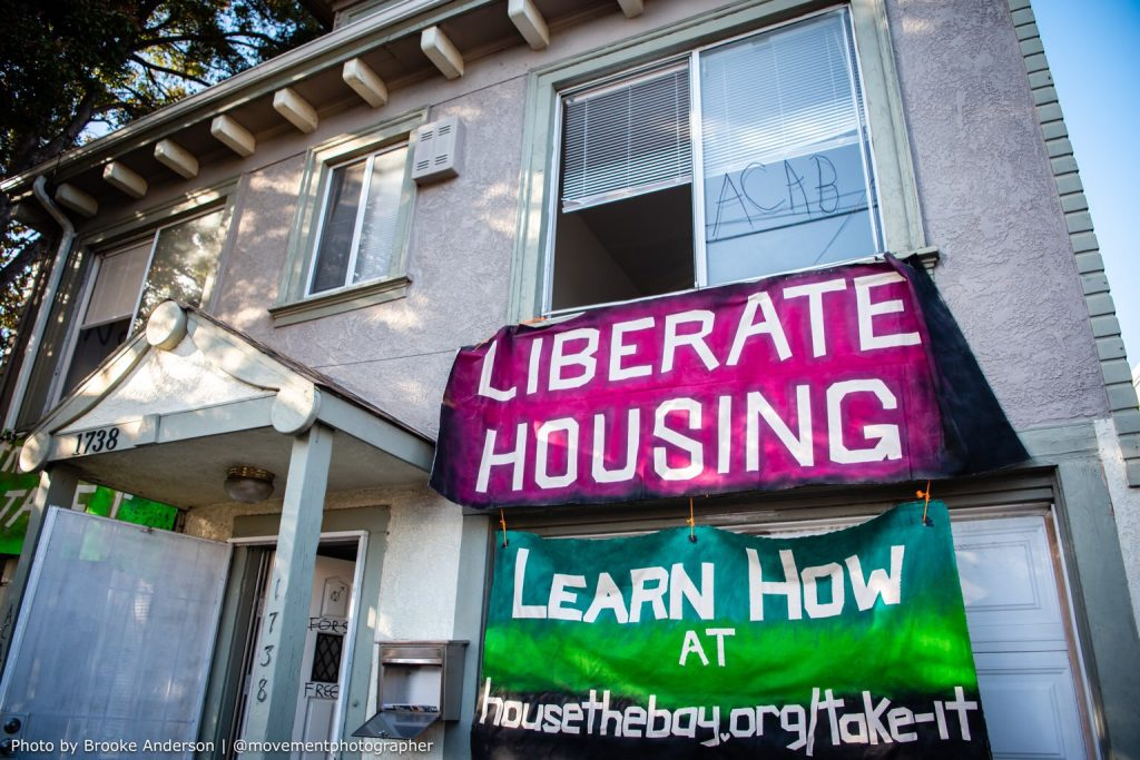 """A vacant home with two huge banners on the side, one reads """"liberate housing"""" and the other says """"learn how at housethebay.org/take-it"""""""