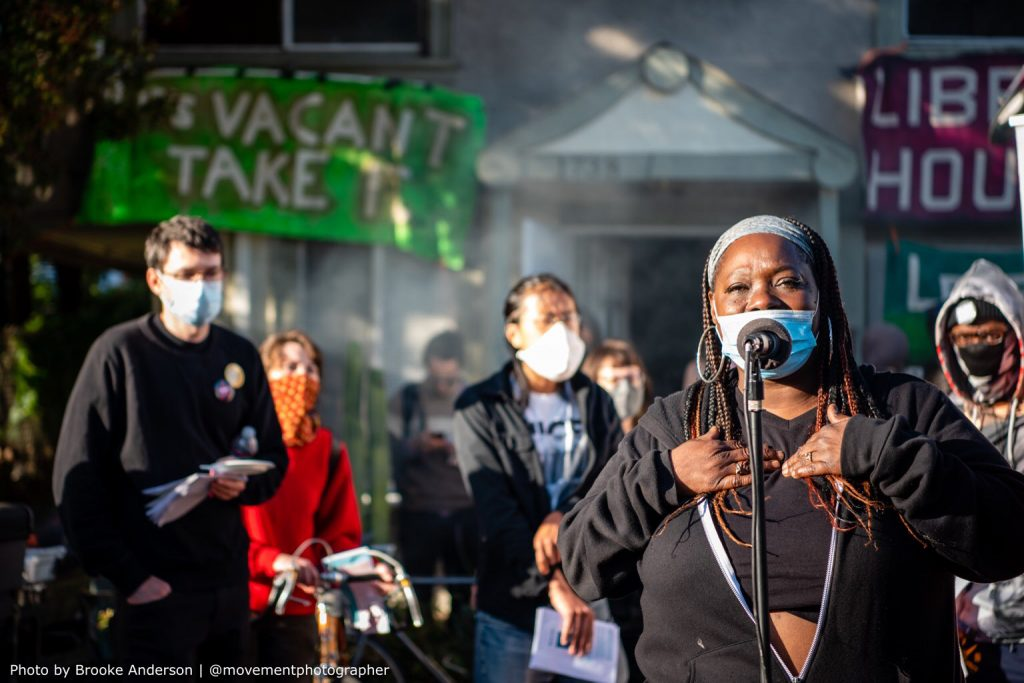 """A Black woman speaks into a microphone in front of the vacant home. She is wearing a surgical mask. People can be seen listening to her speak in the background. In the deeper background, the house can be seen with banners reading """"if it's vacant take it"""" and """"liberate housing"""""""