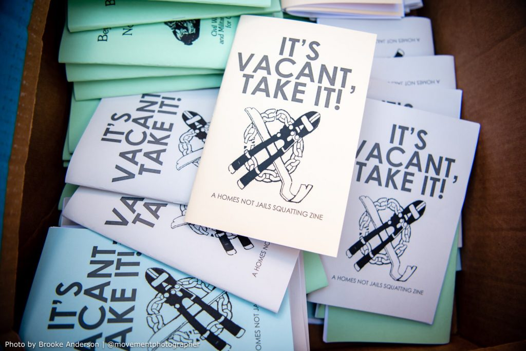 """A pile of zines with the words """"if it's vacant, take it!"""" written on the front."""