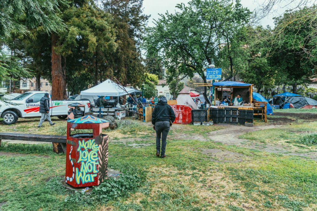 """The people's park community kitchen with tents in the background. In the foreground a trash can is painted with a mural that reads """"make love not war."""""""