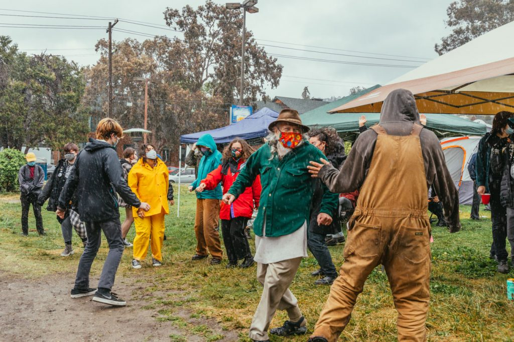People dance in the mud in front of the people's park stage. Raindrops can be seen falling from the sky.