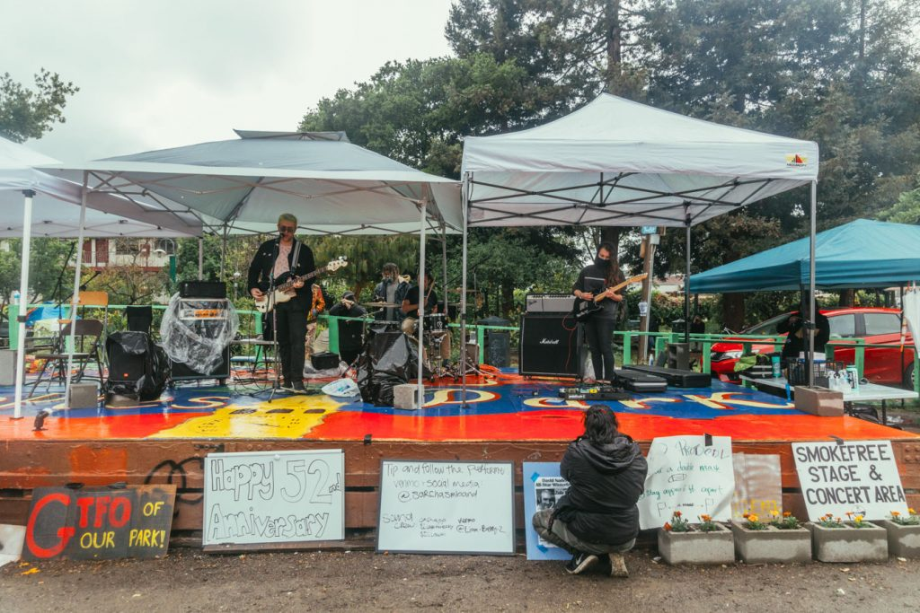 Berkeley-based pop punk band, Sarchasm, plays on the red and blue People's Park stage. The band plays beneath easy ups on the stage to protect themselves and their instruments from the rain.