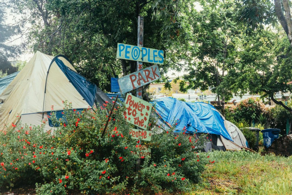 """Tents can be seen behind a series of hand made signs that read, """"people's park, power to the people"""""""