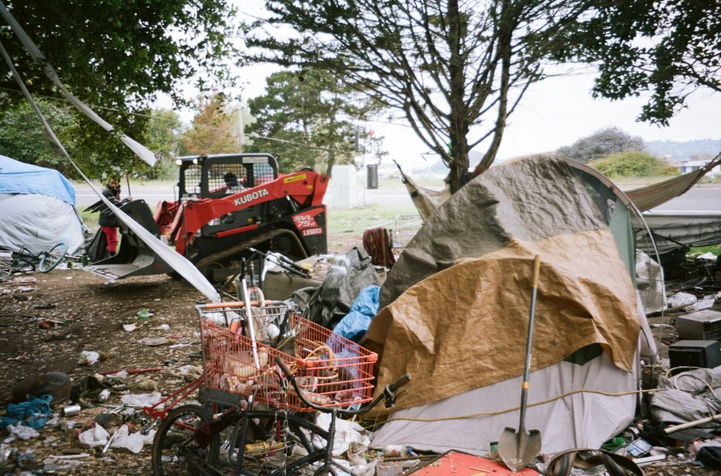 A shovel rests against a tent. Garbage surrounds the tent, and a volunteer can be seen cleaning up in the background.