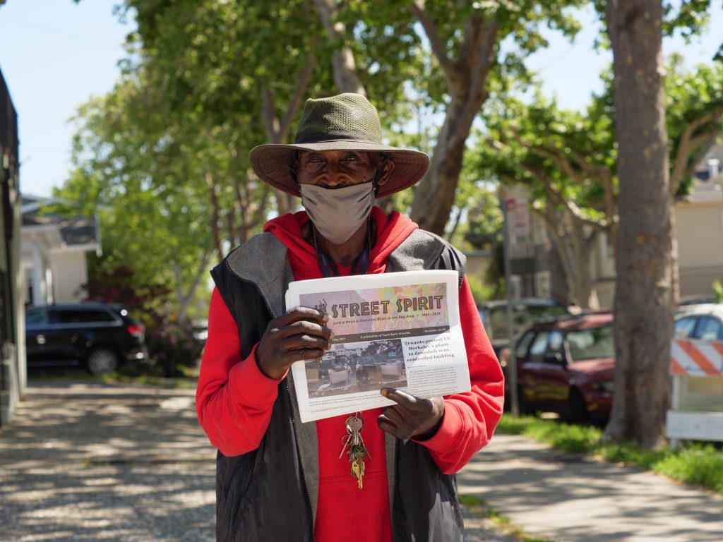 Kevin Aikens, a Black man wearing a red sweatshirt and a floppy hat, holds up a copy of Street Spirit.