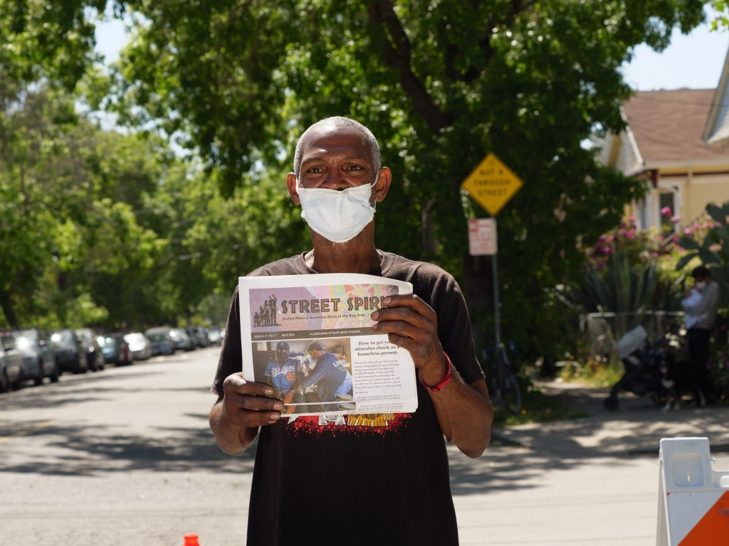 Bobby, a Black man in a black shirt, holds up a copy of Street Spirit with a seemingly residential street behind him.