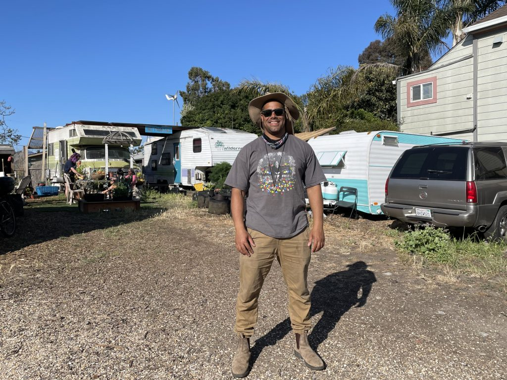 Adam Garrett-Clark stands in the middle of the Neighborship RV community. RVs and cars can be seen behind him. Hr wears work pants and boots, and stands squarely in front of the camera smiling.