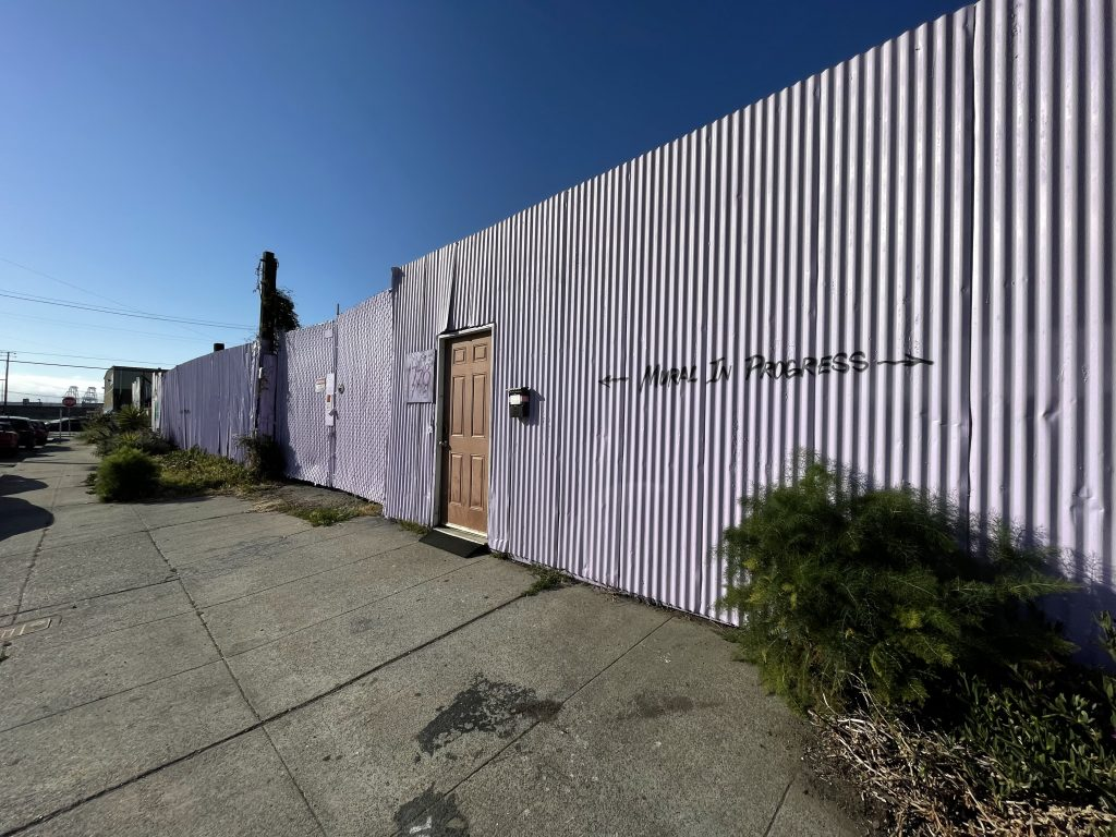 """A powder purple, corrugated fence has a brown wooden door in the middle. This is the entrance to the Neighborship community. The words """"Mural in progress"""" are painted on the fence."""