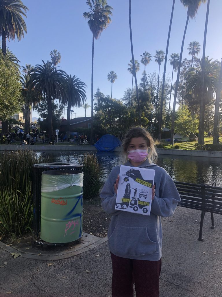 """A masked protestor stands in a Los Angeles public park, with palm trees and a lake in the background. She holds the """"housekeys not sweeps"""" poster in her hands."""