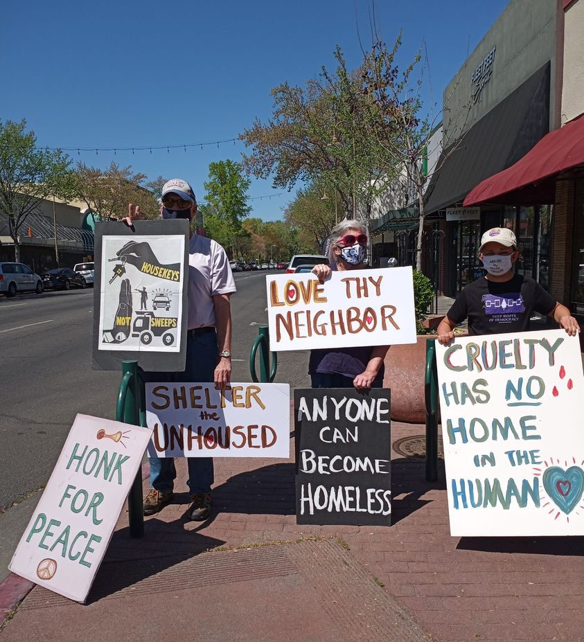"""A group of masked protestors stand on the sidewalk in Chico, CA, with signs that say """"love thy neighbor,"""" """"Shelter the unhoused,"""" """"Honk for peace,"""" and """"housekeys not sweeps."""""""