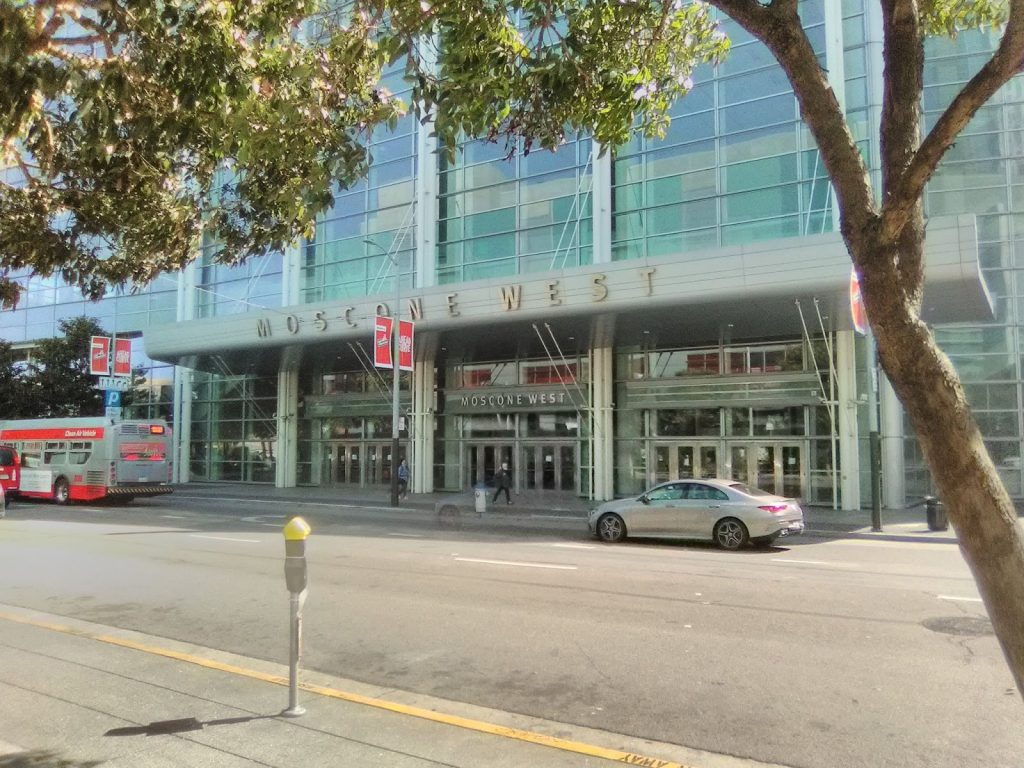 The front of San Francisco's Moscone West building. The building is modern with a blueish glass facade.