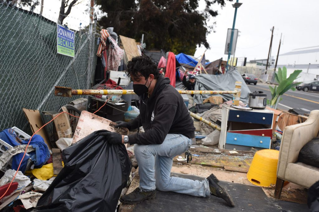 Ian Cordova Morales kneels amidst scattered trash and encampment resident possessions, loading things into black trash bags.