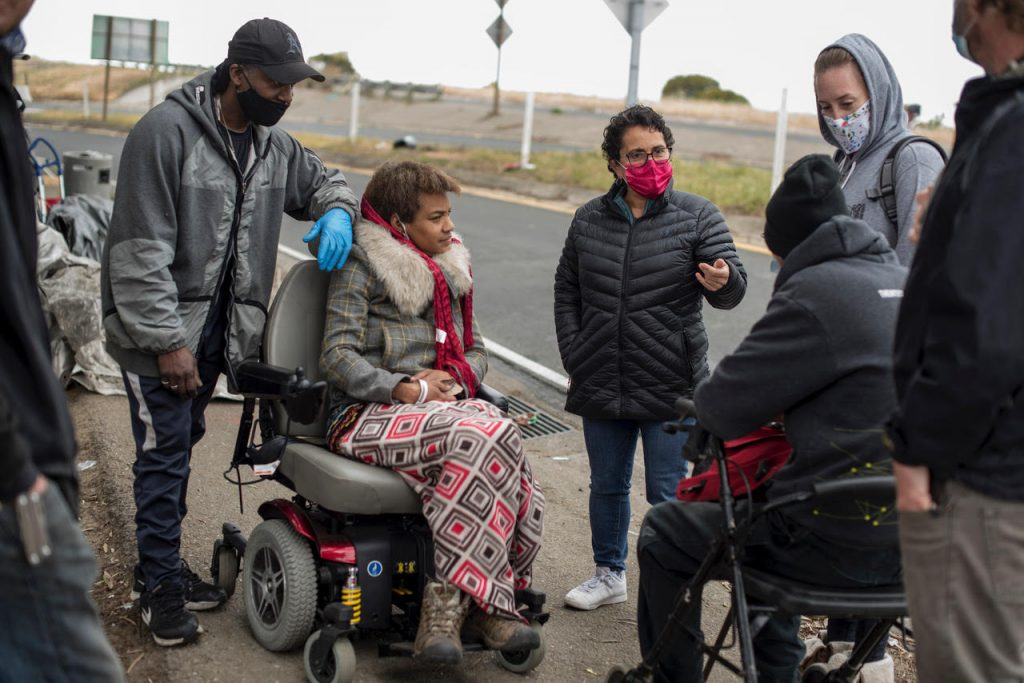 A group of Shellmound encampment residents an their lawyers huddle together in conversation. They are standing next to a freeway exit on the sidewalk, wearing warm jackets and hats.