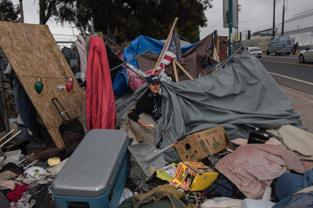 Gabe pokes his head out of his tent. He is surrounded by a big pile of his belongings, as well as trash bags for moving. An American flag pokes out of the refuse behind him. Red and green string lights are attached to his tent.