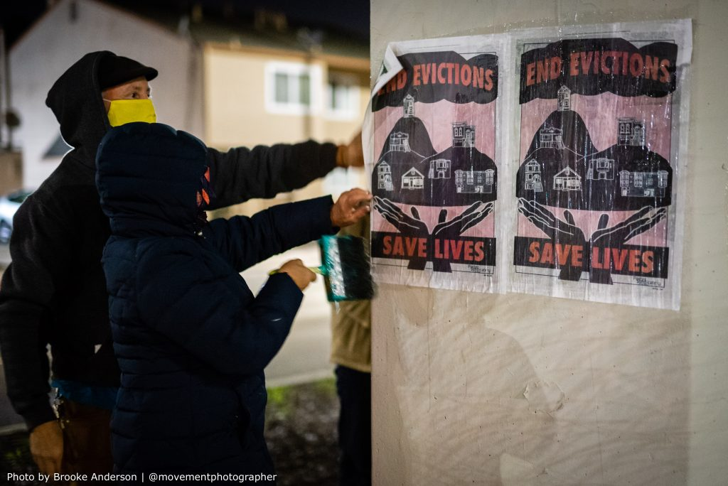 """Two hooded people use wheatpaste to paint a poster that reads """"end evictions, save lives"""" onto a concrete pillar so that it sticks."""