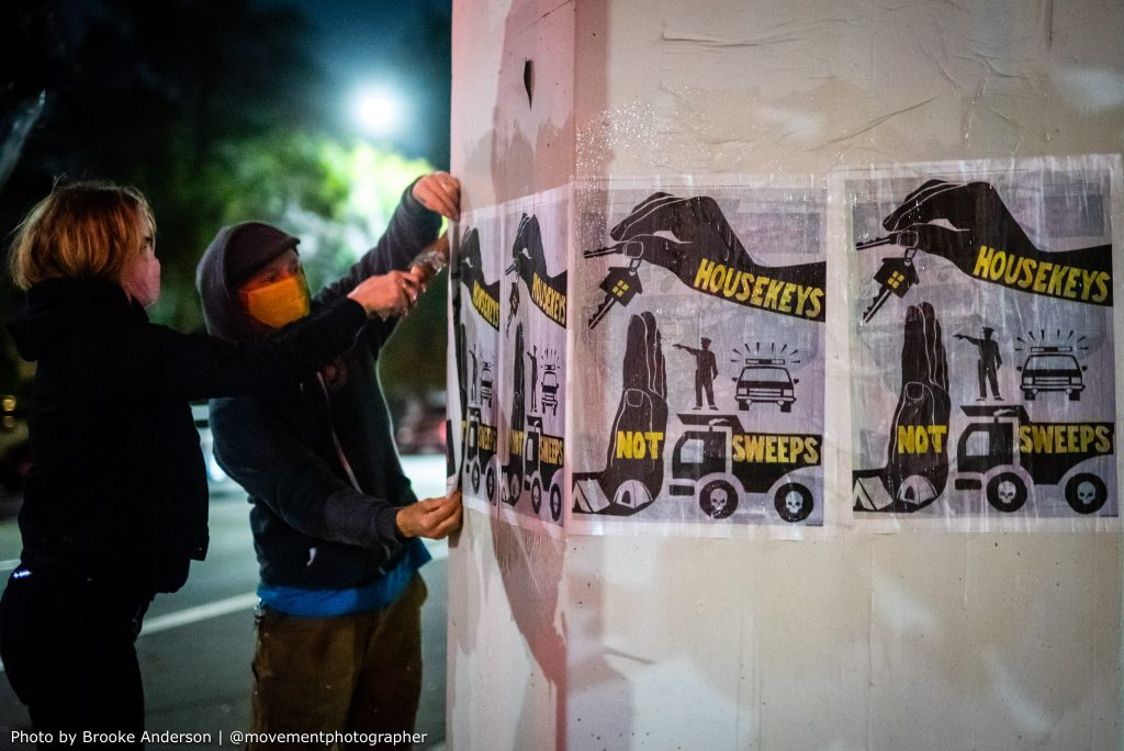 """Two hooded people use wheatpaste to paint a poster that reads """"housekeys not sweeps"""" onto a concrete pillar so that it sticks."""