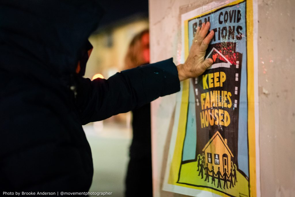 """A hooded figure pushes their hand flat against the """"Ban covid evictions, keep families housed"""" holding it up against a concrete pillar, in preparation to use wheatpaste to stick the poster to the pillar."""