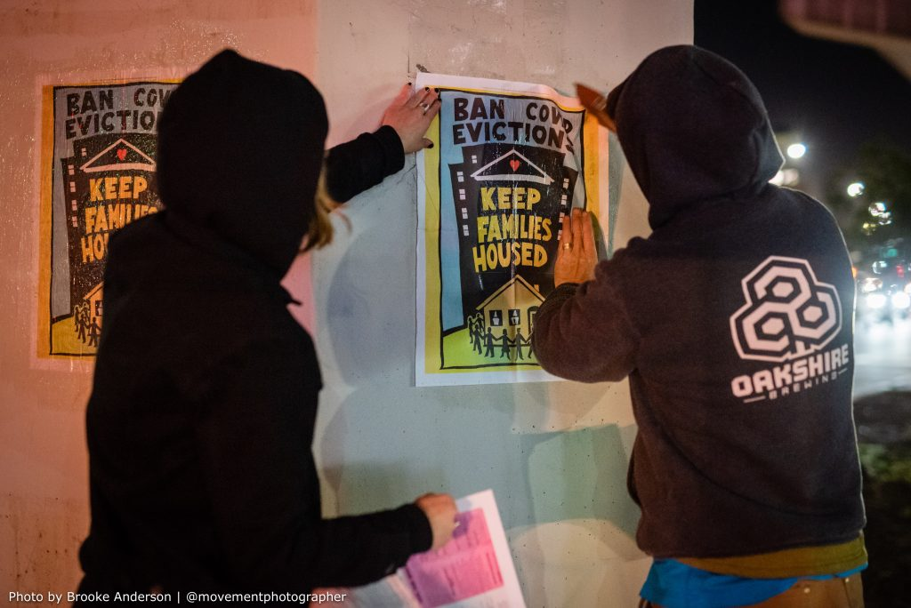 """Two hooded people use wheatpaste to paint a poster that reads """"ban COVID evictions, keep families housed"""" onto a concrete pillar so that it sticks."""