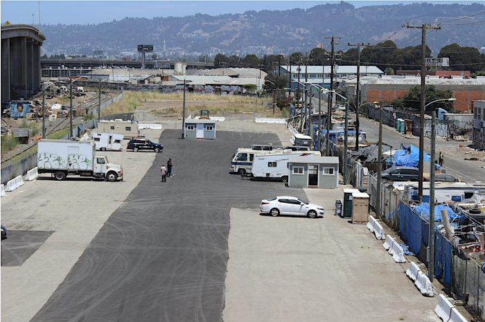 A nearly empty parking lot where the wood street safe parking program takes place. Six vehicles can be seen in the photo and an encampment presses up against the fence that separates the parking lot from the street.