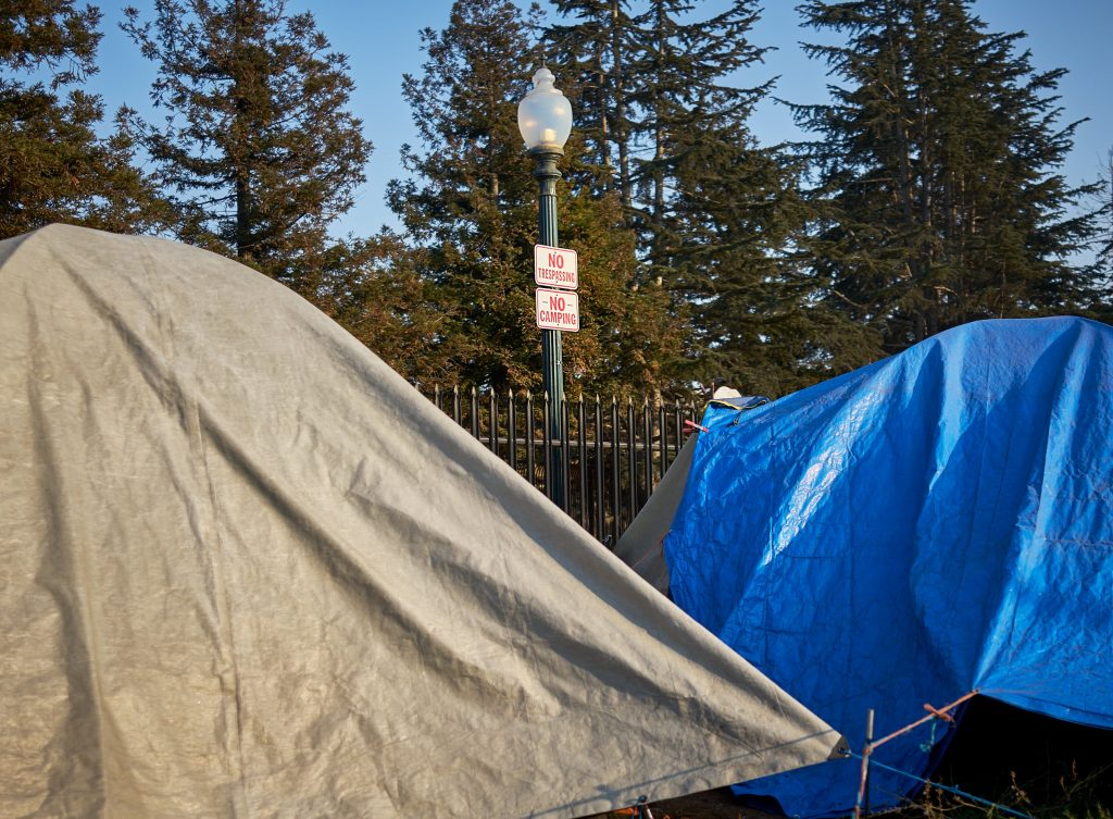 """Two tents set up next to each other at a homeless encampment. In the background, a light post with two signs on it sticks up in between the two tents. The signs read """"No tresspassing"""" and """"no camping."""""""