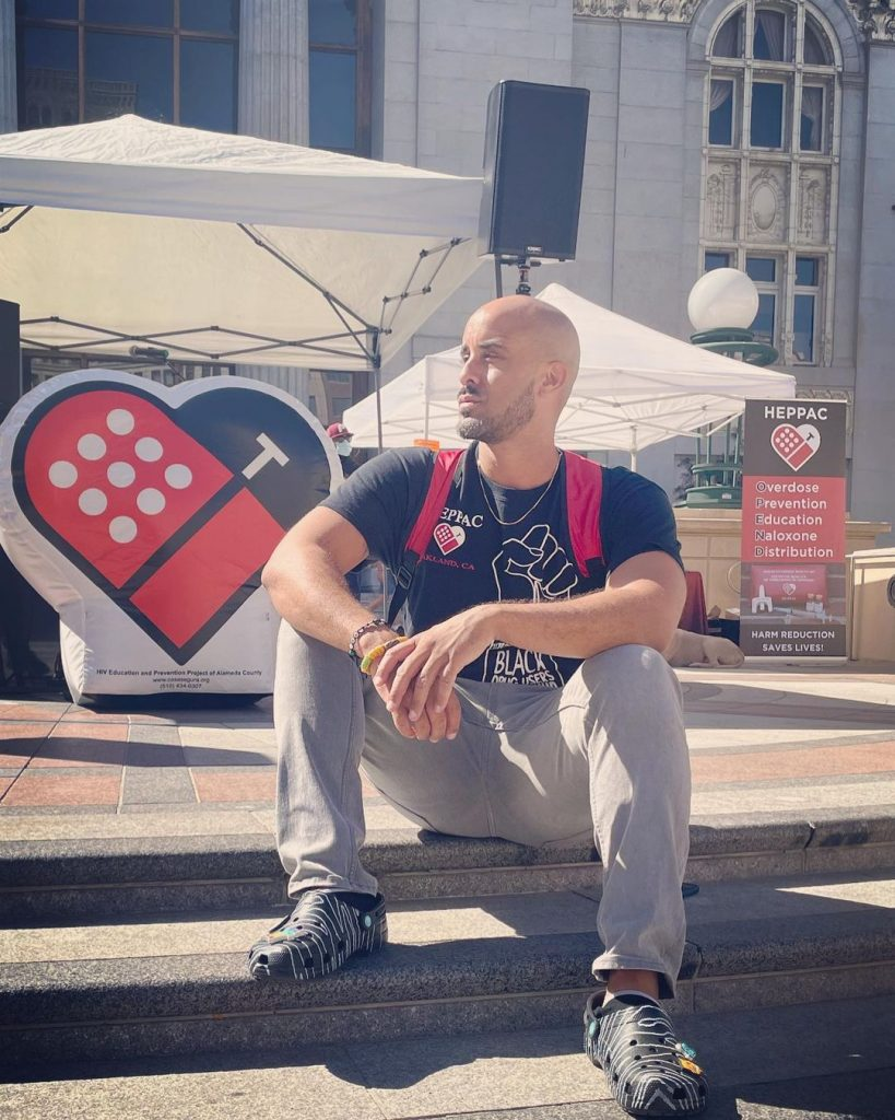 Braunz E. Courtney—a Black man wearing crocks, grey pants, and a black shirt—sits on the steps outside a HEPPAC harm reduction event.