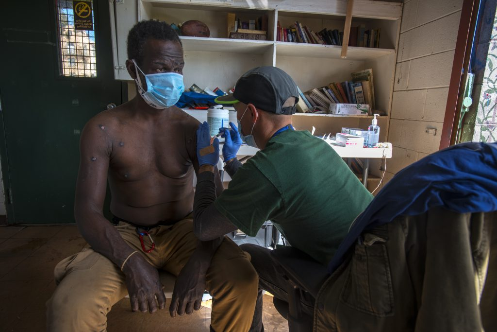 A shirtless man wearing a blue surgical mask gets the COVID vaccine. He has some scars on his chest.