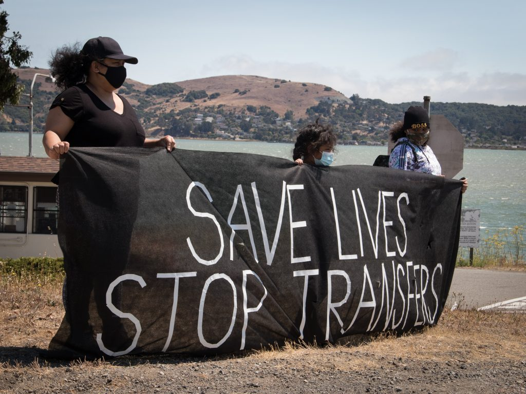 """Three people hold a banner that says """"save lives stop transfers"""" with San Quentin and the ocean in the background."""