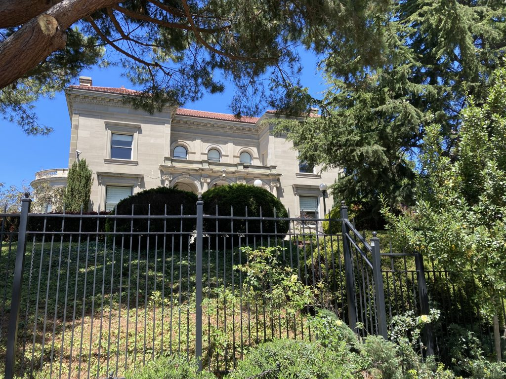 The chancellor's mansion at UC Berkeley stands tall behind a black metal fence.