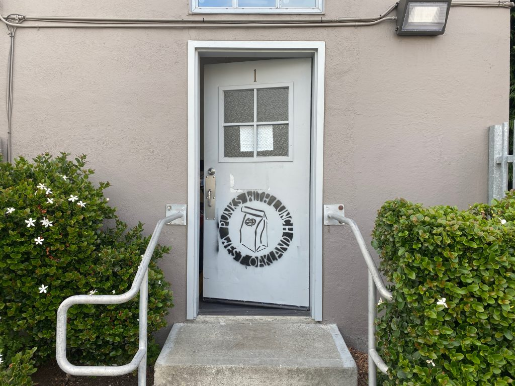 """The door to the Punks With Lunch office, with their logo spray painted on the door. The logo is a paper bag with the anarchist symbol """"A"""" on the front. The bag is surrounded by the words """"West Oakland Punks With Lunch"""""""