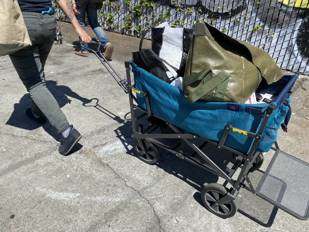 A person wearing grey jeans and black sneakers pulls a blue cart containing bags of Narcan and other harm reduction supplies.