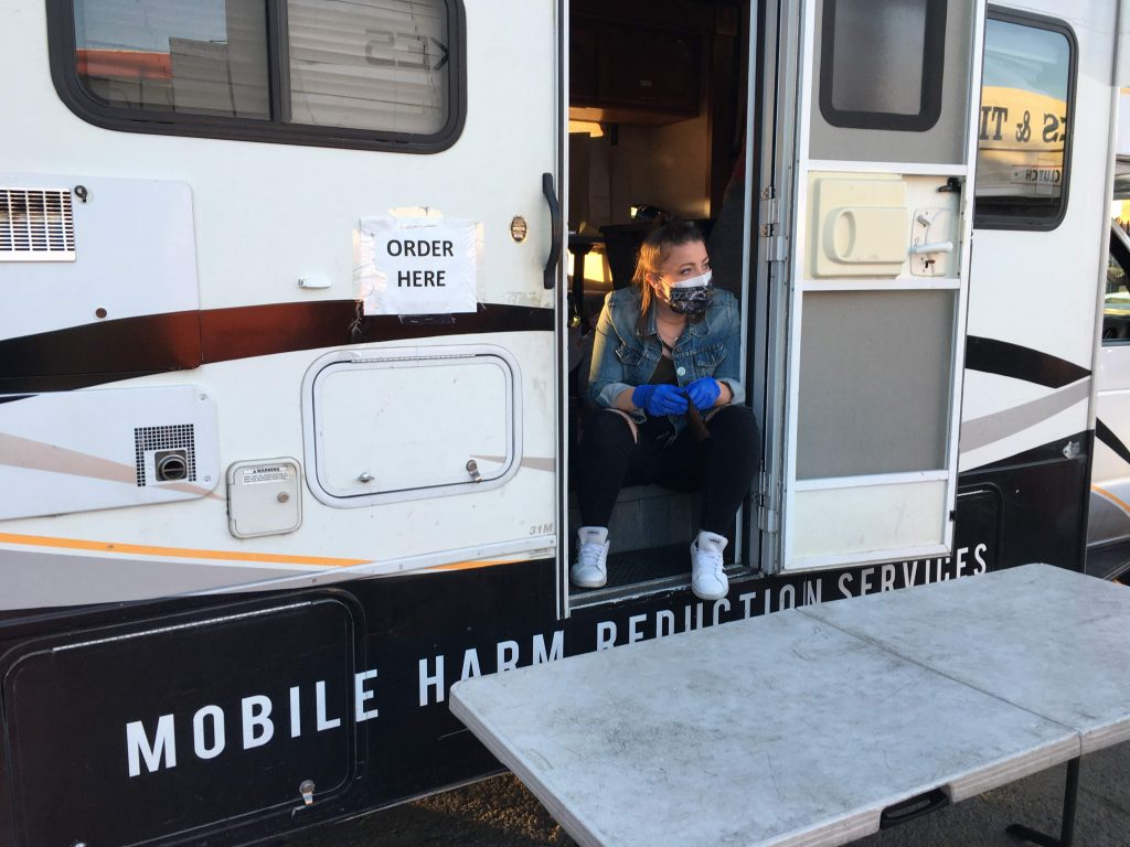 """A woman sits on the stops an RV with the words """"mobile harm reduction services"""" written on the bottom. She  looks out into the distance, wearing blue gloves and a mask. A sign that says """"order here"""" is taped onto the side of the RV."""