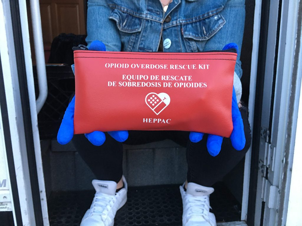 """A pair of blue gloved hands holds a red pouch with the words """"opioid overdose rescue kit"""" written on the front."""