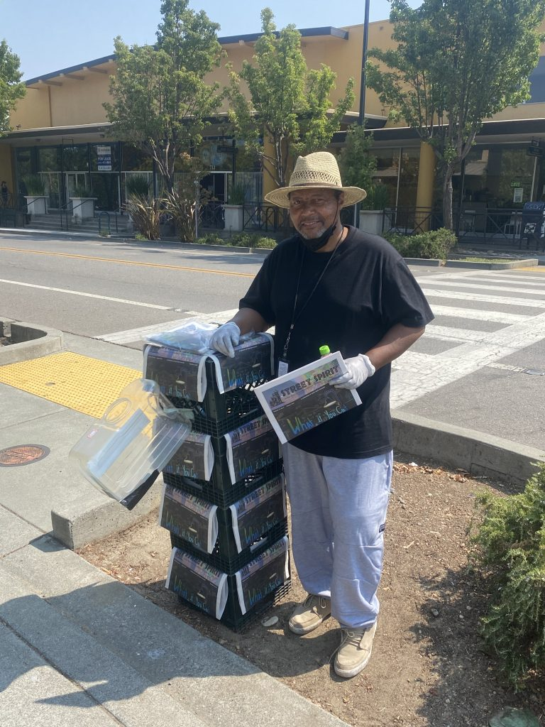 Vernon Dailey stands on the corner with crates displaying his newspaper. He is wearing a black t-shirt, a straw hat, grey sweatpants, and lace up leather sneakers.