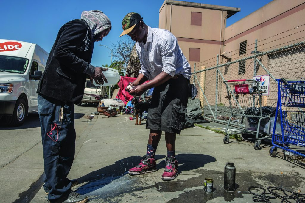 One man washes his hands with a bar of soap while another pours water over his hands from a plastic gallon container. They are standing on the sidewalk and shopping carts and a dog can be seen in the background.