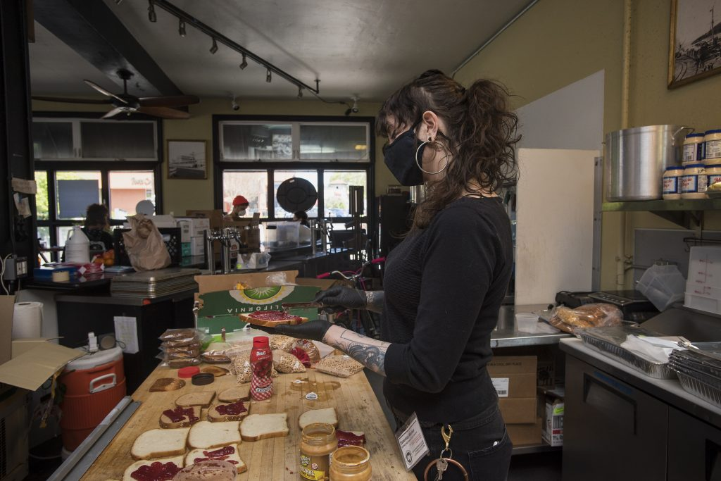 A woman in black spreads jelly on a piece of bread. Several pieces of bread with jelly and peanut butter lie on the table before her, waiting to be assembled into PB&J sandwiches.