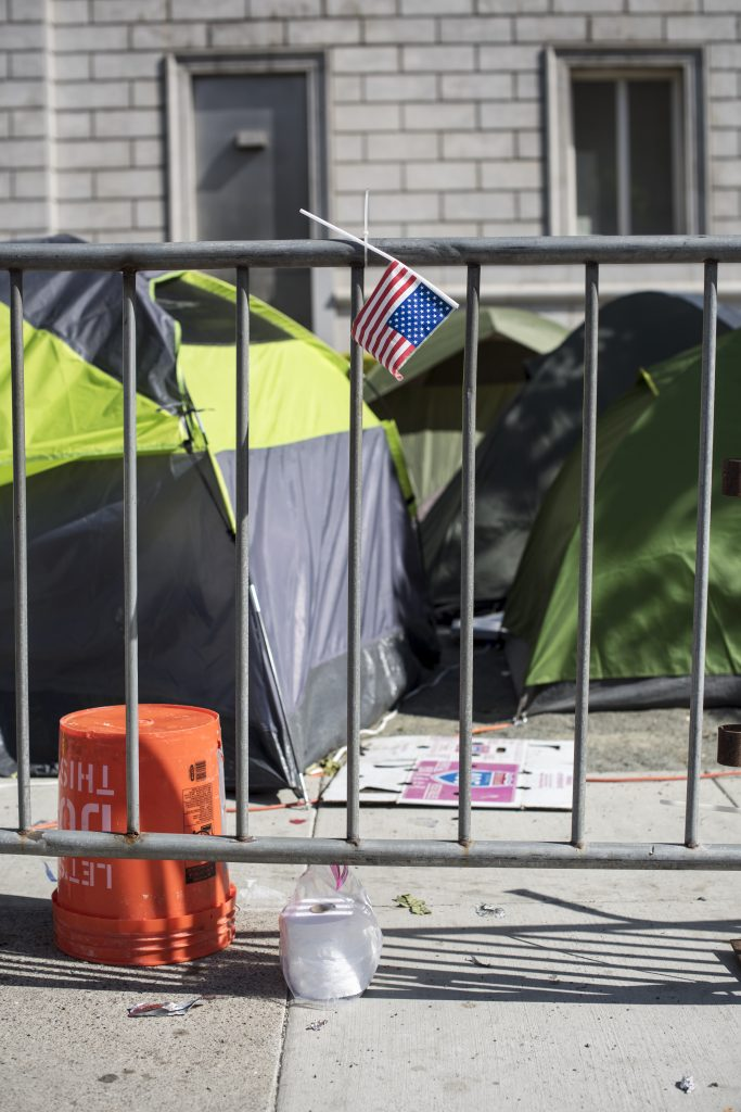 two green tents behind a metal fence.