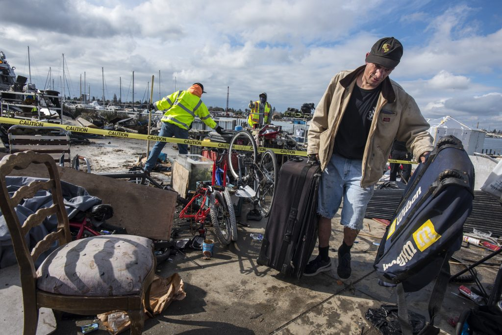 A man holding two suitcases walks away from his homeless encampment. Behind him, a pile of bicycles and old chairs sit behind a line of yellow caution tape. Two public works employees in neon vests work on removing items from the area.