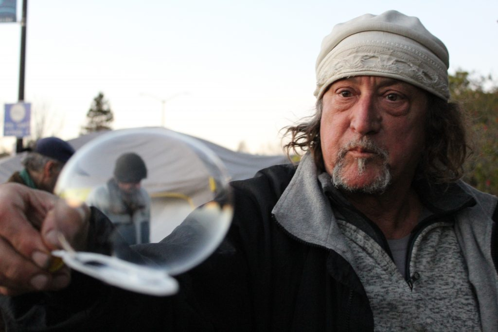 Robin holds a bubble wand out toward the camera, with a bubble balanced on top. He is wearing a grey sweater and a white hat.