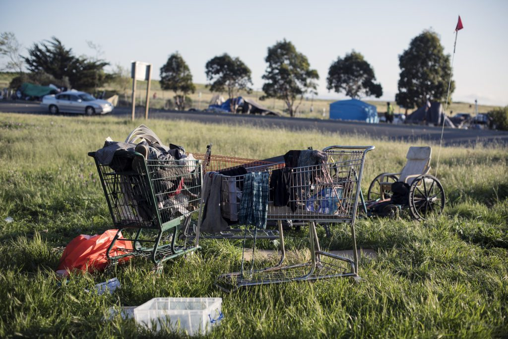 Shopping carts full of clothes and other belongings sit in a grassy patch next to a highway offramp. A wheelchair can be seen in the background.